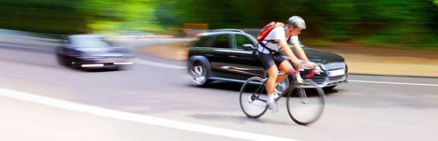Ciclista con coches adelantando